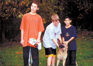 "Meeting ""new"" friends and making memories at Camp Potawotami.  Pictured from right to left; Jesse Dominquez, ""Freddie"" (one of 4 dogs and 2 pot-bellied pigs kept at camp), Jordan Cornwell, and Alex Cornwell."