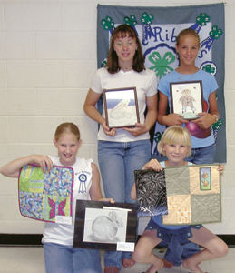 Blue Ribbon 4-H Club Members (l to r) Megan Powers and Rachel Powers (standing), Leah Wolfe and Anna Schutt (kneeling) displaying their Quilting and Arts and Craft projects.