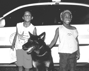 "Canine ""Zorro"" enjoying the evening with Korey and Kameron Joyner during National Night Out.  Zorro's handler is Officer Lowden."