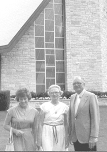 (L to R) Lois Oetting, Alma and Harold Hollman in front of church windows designed by Harold's business, City Glass Specialty (church is in Grafton, WI).
