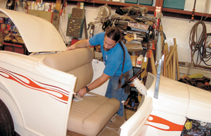 Marcus Marquart places the newly upholstered seat in a 1932 Ford Roadster.