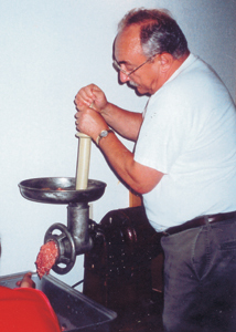 Herman Quake grinds the fresh pork for the making of bratwurst.