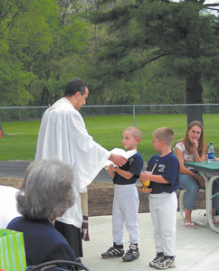 "Grand Opening for ""The Stand"" was held on Friday, April 30th.  (L-R) Included in the Grand Opening was a Dedication, prayer, and blessing by Father Joe Rulli, along with alter boys Matt and Mick Palmer from St. Therese."