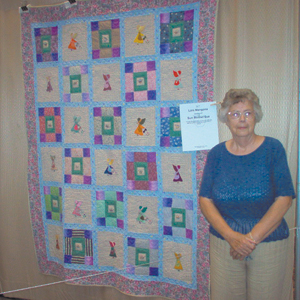 "Lois Mangona stands next to her ""Sunbonnet Sue"" quilt in the Grand Wayne Center, during the Three Rivers Quilt Festival."