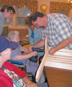 Resident Jean Fortney helps with chair assembly. Her son, Dan Fortney watches as volunteers Carol Briggs and Larry Frazee help guide the drill.