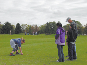photo by Cindy Cornwell After teeing up Travis Adamonis hits the green with his drive. (L-R) Looking on are Asia James, Alex Colehin, and Mr. Mark Hageman.