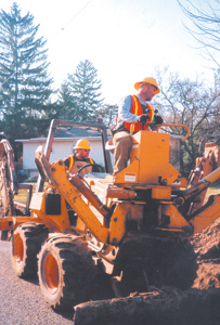 Rod Mayo, top and Nick Fisher operate a combination trencher and backhoe at 2427 Allegany Avenue on March 24, 2005.  The trencher digs the trench, the four-inch orange conduit is placed in the ground and the backhoe covers it up.  Two men, on hand shovels, do the clean-up work and later another crew will pull up to three black fiber-optics cables through the four-inch trace.