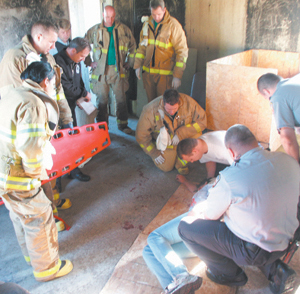 "photo by Susan Banta Tony responds to an ""unknown medical condition"" call for a patient on the 4th floor of a building.  Tony, kneeling in the center, 4th from right, listens as the patient provides answers to questions in this emergency simulation."