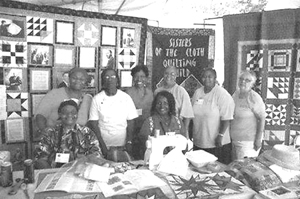 Members of the Sisters of the Cloth Guild are all smiles at their quilt display at the Folklife Festival in Washington DC.