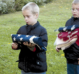 L-R Cub Scouts Kendrick Marcum and Alexander Edwards prepare for retiring their flags.