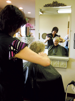 Co-owner Kathy Freiburger styles customer Helen Muntzinger's hair at the Hair Affair Spring Social.