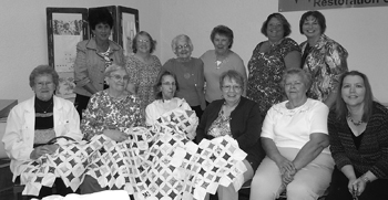 Members of the Lamplighters Homemakers Club and the cathedral window quilt started by the late Mary Wilhelm.