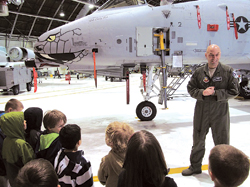 Major Brad Reynolds talks to the preschoolers in front of the A-10 fighter jet.