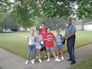 Officer Wiley talks to kids waiting for the Kekionga bus, L-R,  Kelsey Lytle, Jessica Jacobs, Jessie Keesler, Shanon Thorn and Johathon Stantz