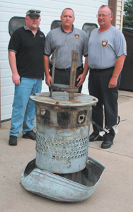 Captain Tim White, Doug Paulson and Captain Dave Redding stand behind the old whistle on Old Trail Road.