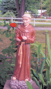 SAINT FRANCIS' ROSE photo by Lois Mangona Mornings always begins with a walk around our garden. This past July we noticed that a single rose bud had found its way through the arms of our Saint Francis statue. My husband (Frank) and I were thrilled to find this gift of beauty from Saint Francis.