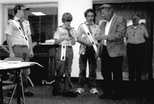 Scout John Dukarski watches as Scout Rob Dukarski and Scout Brian Shawver receive Press Corps awards from Editor Bob Stark. Miami District Commissioner Earl Kumfer observes the awarding.