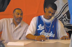 Waynedale News file photo James Hardy, of Elmhurst High School commits to Indiana University in both football and basketball on Wednesday, February 4, 2004 in the Elmhurst High School Community Room.  Hardy's father, James Hardy II, witnesses the event.