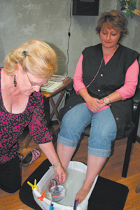 Marcy Long of the Hair Company sits back and relaxes as Lois Skelly from Sole Energy activates the relaxing and healing footbath.