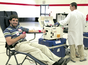Honoring a tradition of giving blood since he was a junior in high school, Daniel Davis was a double red blood cell donator. Shaun, with the American Red Cross, monitors the Haemonetics machine during the procedure.