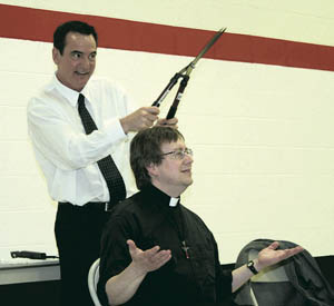 """Students at St. Therese chant, """"Mohawk! Mohawk!"""" as Jeff Hey from the Hair Barn holds up a pair of pruning shears for Father Dave's haircut."""