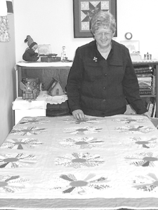 Marty Haag proudly stands by her quilt-in-progress, a re-creation of the one she made with her mother in the 1940s.