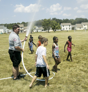 "The participants of Holy Scripture Lutheran Church's ""Bible Soccer Camp"" get hosed down by Southwest Station 1 Fire Fighters Tom Goodwin and Doug Scott at the Church's soccer fields. The temperature soared to over 100 degrees on Wednesday, July 22, 2011."