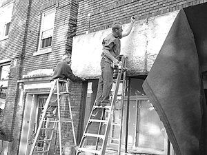 John Stiffler and Herb Hernandez remove the former building sign on a beautiful October afternoon.